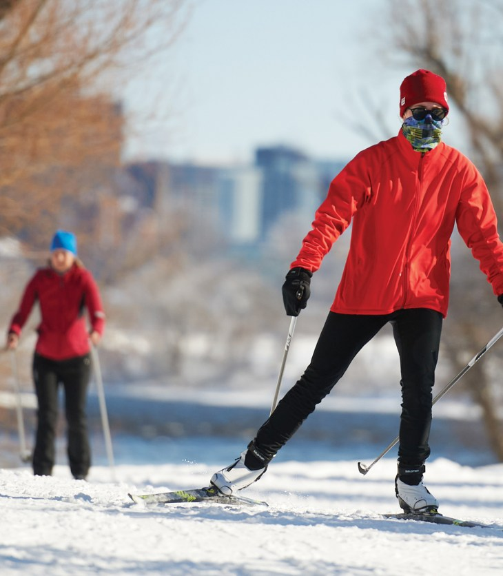 A skier wearing a red jacket, black pants and a face mask is seen up close on the winter trail on a sunny day