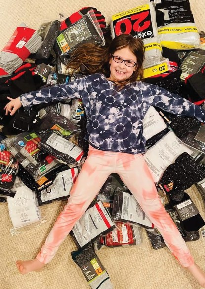 An 8-year-old girl lays on top of a pile of items to be donated like socks and mittens