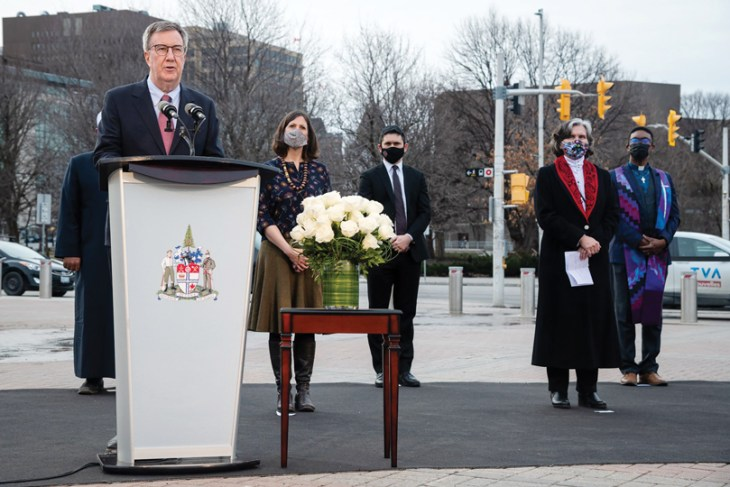 Mayor Jim Watson stands at a podium outside city hall on an overcast day in Ottawa with religious leaders standing behind him standing six feet apart and wearing masks