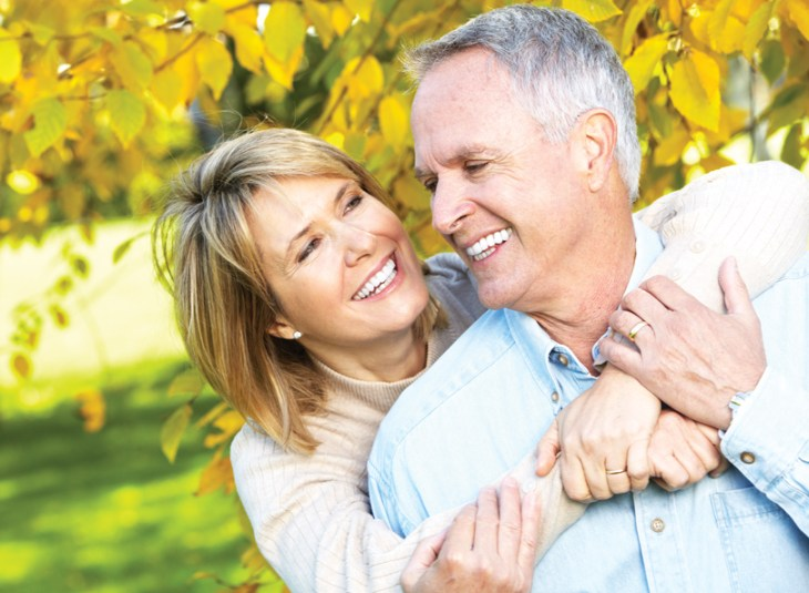 A woman and man embrace against a yellow and green fall foliage background