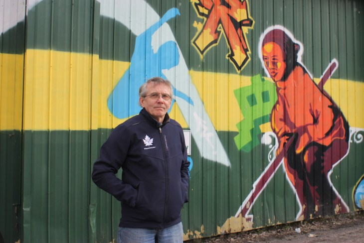 A man stands in front of a wall of graffiti on Scott Street outside the curling club