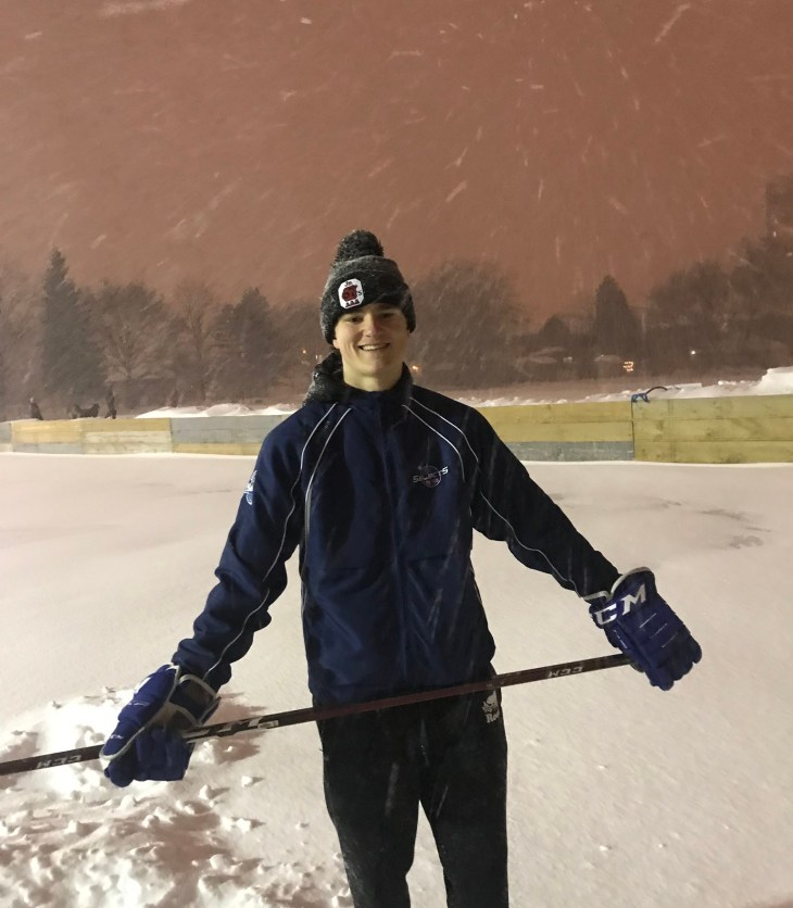Owen Hollingsworth stands on a snow covered rink during a snowy evening in Ottawa and he holds a hockey stick
