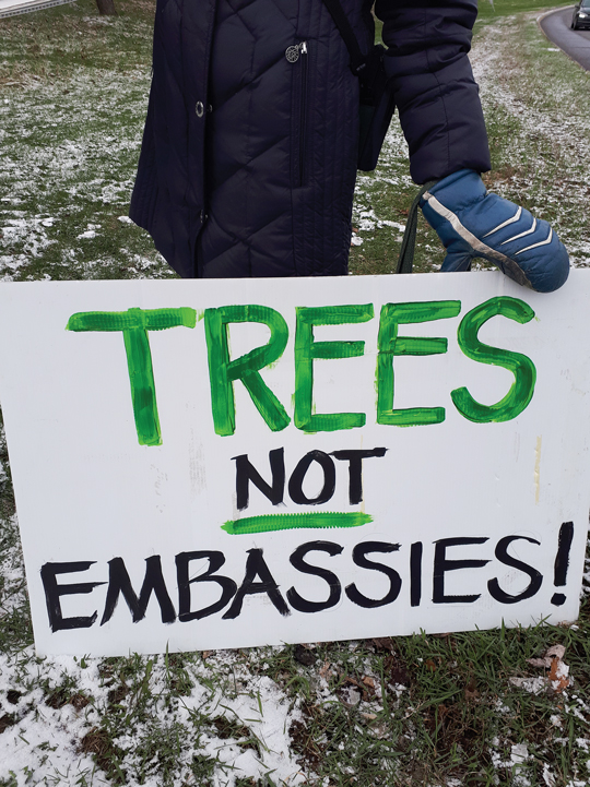 "A white protest sign is held up by a gloved hand. The sign reads ""trees not embassies"" in green and black lettering."