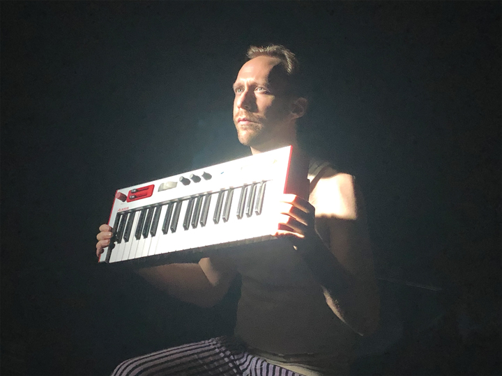 Scottie Irving sits on a dark stage and holds up a keyboard in the lights