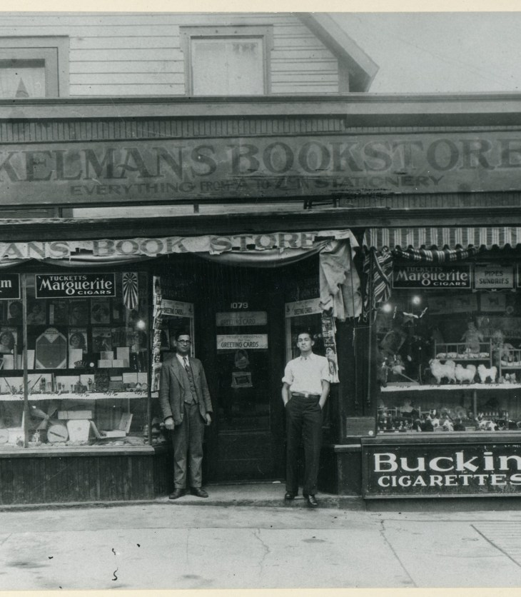 A black and white photo from 1935 showing two men standing outside of Kelmans Bookstore on Wellington West Street