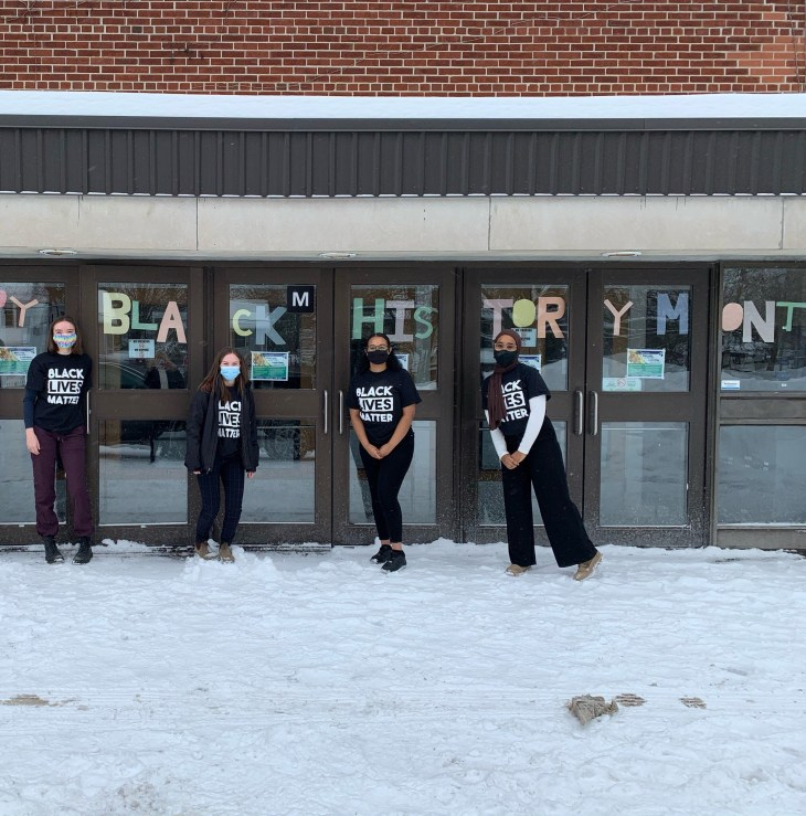 Four students stand outside of Nepean High School on a snow covered field wearing Black Lives Matter t-shirts for Black History Month