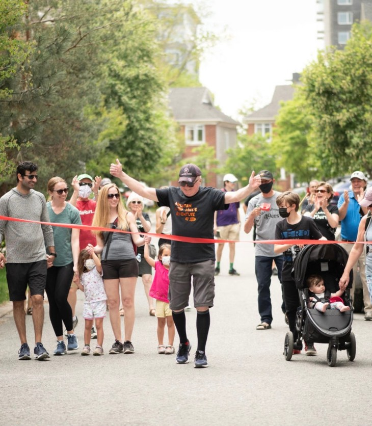 Michael Baine is seen with his family crossing the red ribbon finish line for his half-marathon walk in Westboro