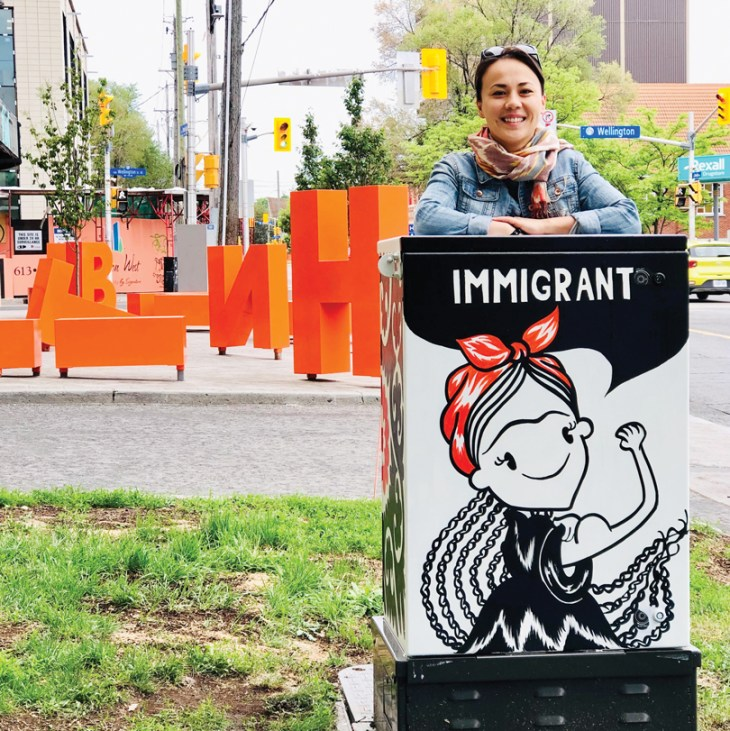 """Kseniya Tsoy stands next to a painted Bell Box at the corner of Parkdale and Wellington West. The painting is black and white and shows a woman wearing a red bandana with the word """"Immigrant"""" above it."""