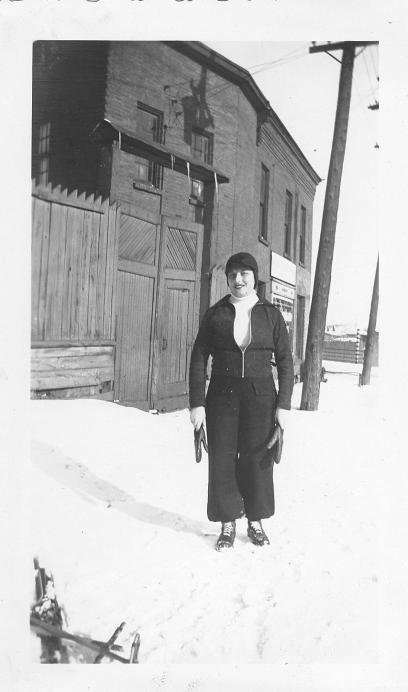 A black and white photo of Fae Taller standing on a snowy Bayview Road in the 1930s in Hintonburg.