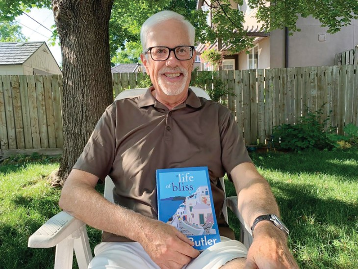 """A man sits in a chair in a yard in Ottawa holding a book called """"A Life of Bliss."""" There is a wooden fence and tree behind him and it is a sunny day."""