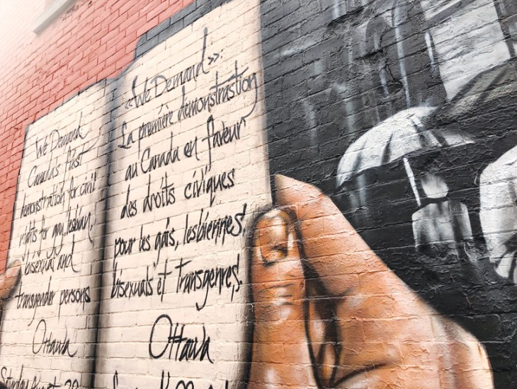 """The """"We Demand"""" mural on a brick wall in downtown Ottawa. In the mural, hands are seen holding up a book with text written over it."""