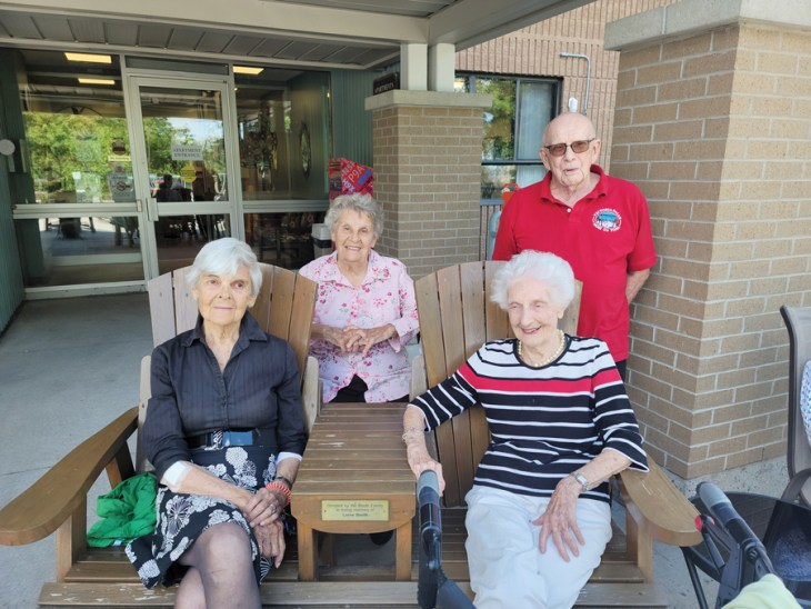 A group of seniors sit outside of Unitarian House on a sunny day in Ottawa