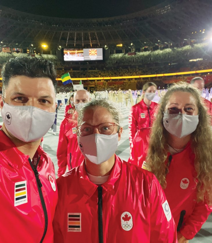 A group of three Olympians wearing Team Canada jackets stand in a large arena in Tokyo