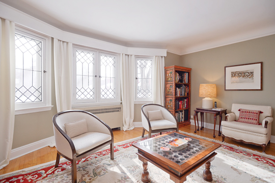 A living room of an historic home is pictured with vintage white chairs and a wood table and bookshelf