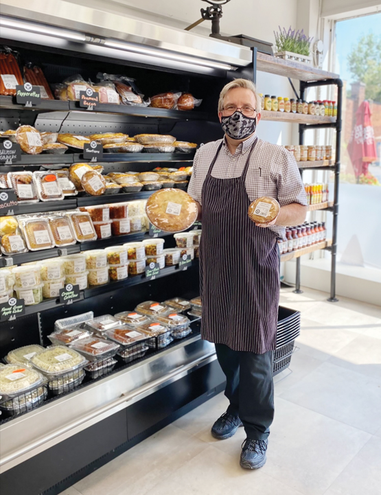 A man wearing a mask and butcher's apron stands in a story and holds up meat pies