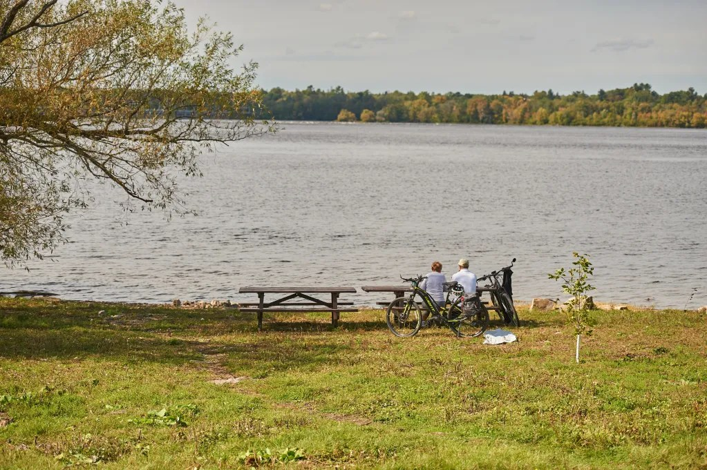 Two people sit at a bench and take a break from their bike ride along the Ottawa River