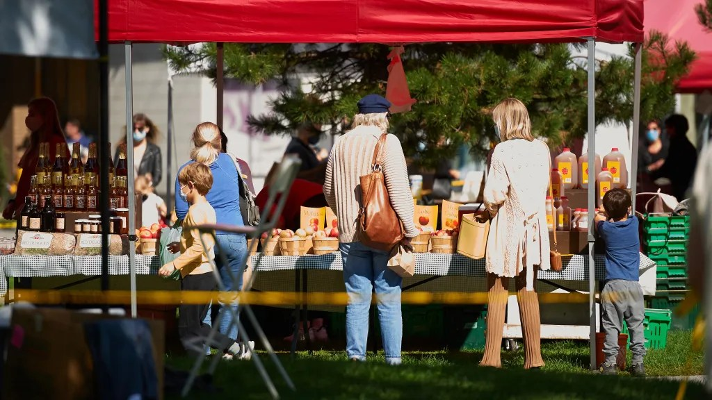 People are seen standing at a farmers' market stand in Hintonburg with apples and apple cider in the background