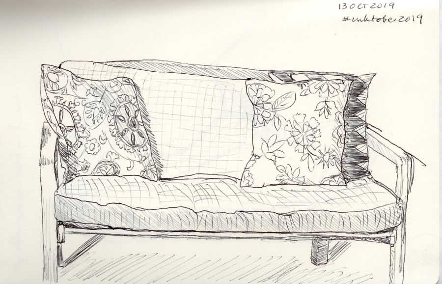 Black and white ink drawing of a couch with three pillows. Drawing by Kit Dunsmore