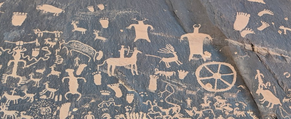 Orange petroglyphs on black, small section of Newspaper Rock in Utah. Photo by Kit Dunsmore.