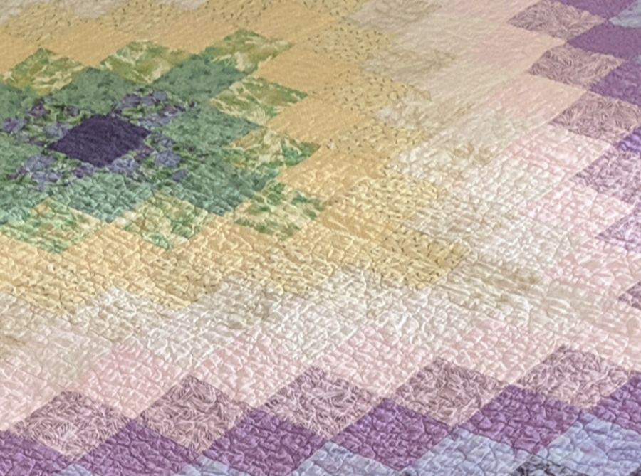 Close-up of pastel trip around the world with stipple quilting. Quilt by Kit Dunsmore