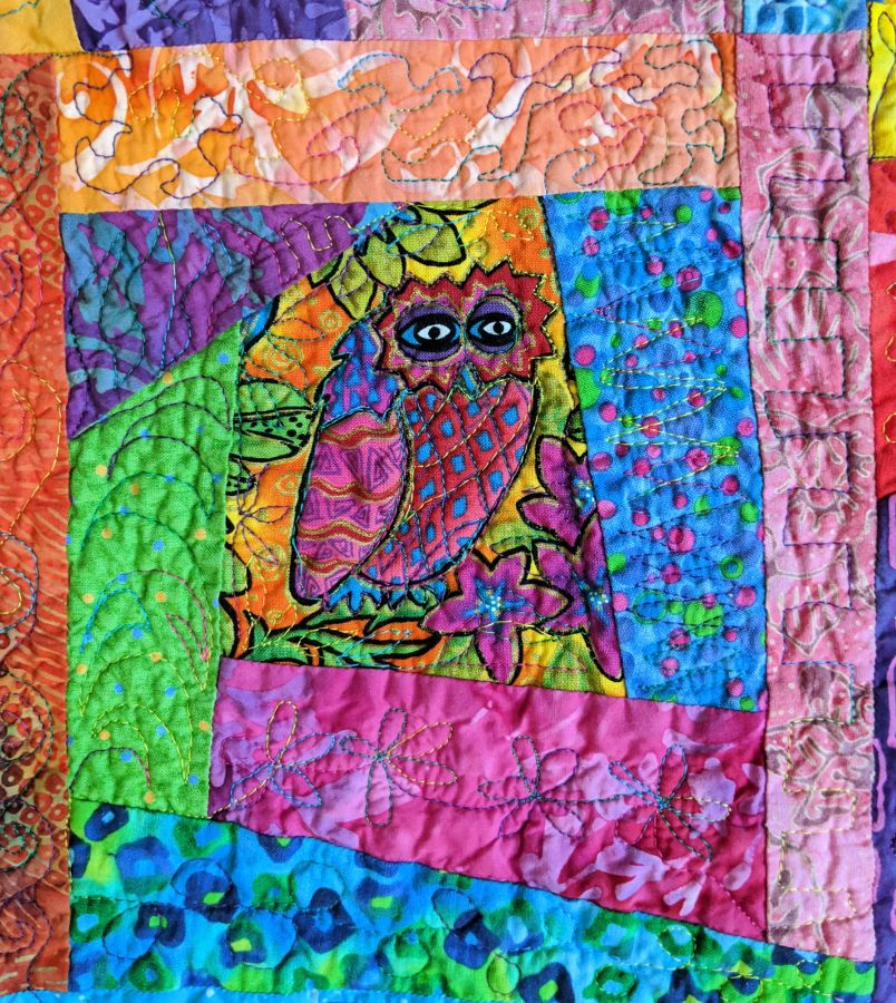 Wonky log cabin block with owl in center in bright candy colors. Quilt by Kit Dunsmore