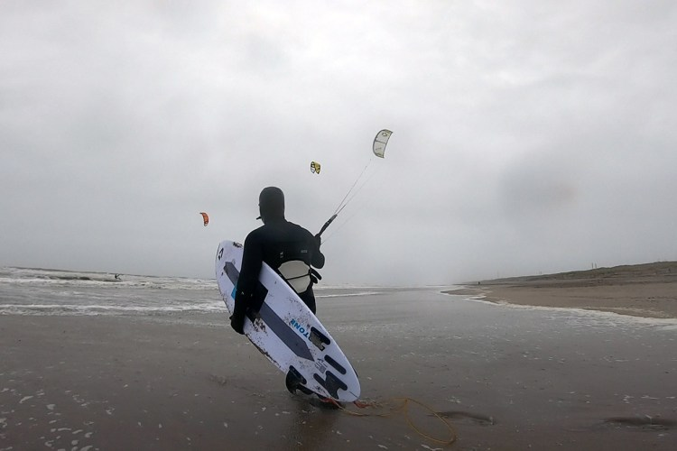 Kitesurfing in January in the Netherlands with cap, shoes, gloves on