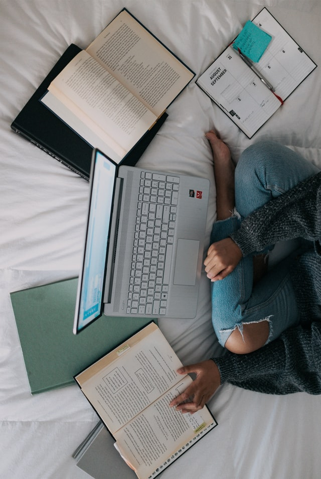 woman doing research on Macbook in bed