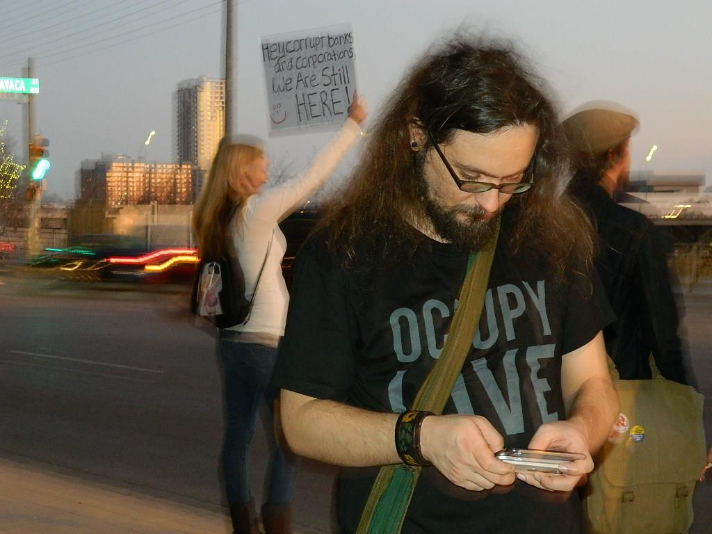 Kit O'Connell livetweets during an Occupy Austin gathering at Austin City Hall, 2011. In the background, activists hold banners and signs for passing traffic.