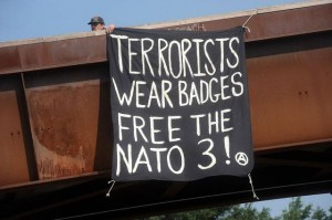 Banner Drop: Terrorists Wear Badges. Free the NATO 3!