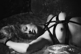 A topless woman lounges in a rope harness.