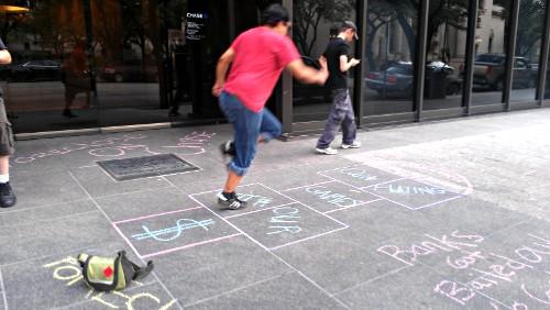 An occupier plays hopscotch on a chalk covered sidewalk.