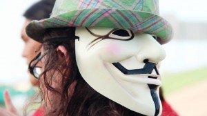 Kit O'Connell wearing an Anonymous mask on the back of his head, under a green hat.