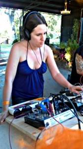 A woman uses the Noise Explorer 5000, flipping knobs while wearing headphones