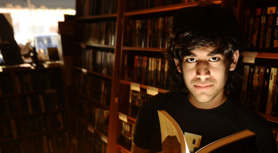 Aaron Swartz holds a book while reading in a library. (Noah Berger)