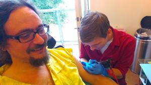 Kit in a yellow shirt sitting in a chair while James works on his arm with the tattoo machine.