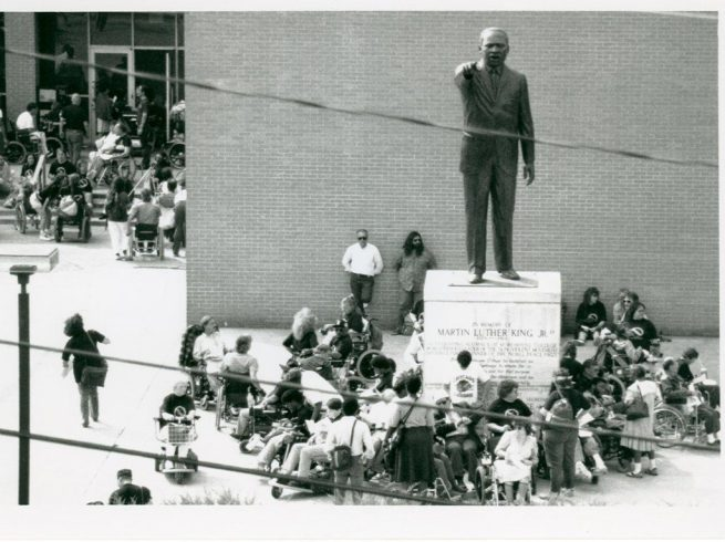 ADAPT disability activists surround statue of Dr. Martin Luther King Jr. and reinforce disability rights as a civil rights issue. (Smithsonian Institution / Tom Olin)