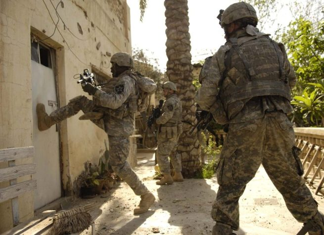 A U.S. Army Soldier from the 1st Stryker Brigade Combat Team kicks in the door of a building during a cordon and search in Buhriz, Iraq, March 14, 2007. (Flickr / U.S. Air Force / Staff Sgt. Stacy L. Pearsall)