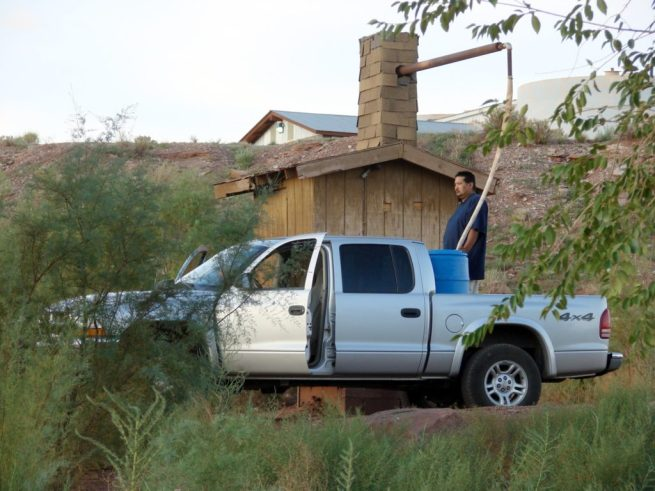 A Navajo man fills a water tank in a pickup truck at a trading stop in Cameron, Arizona on August 31, 2008. (Flickr / Don Graham)