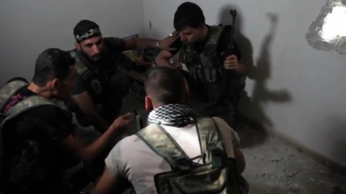 Free Syrian Army soldiers hold a planning session in a bombed-out building during the Battle of Aleppo on October 19, 2012. (Wikimedia Commons / Voice of America / Scott Bobb)