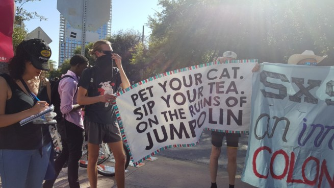 """In this March 13, 2016 photograph, activists hold a banner reading """"Pet Your Cat, Sip Your Tea, On The Ruins Of Jumpolin."""" (Kit O'Connell)"""