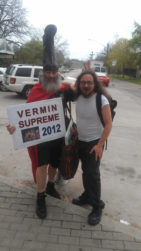 "Vermin Supreme, wearing his trademark boot hat, holds a ""Vermin Supreme 2012"" sign while posing next to Kit O'Connell. (Lainie Duro)"