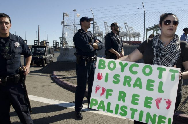 """In this Aug. 16, 2014 photograph, a woman with a """"Boycott Israel, Free Palestine"""" sign stands in front of a police line at the Port of Oakland. (Flickr / Daniel Arauz)"""
