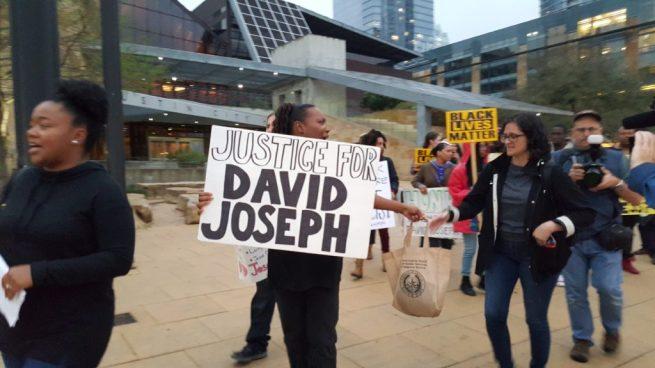 """A Black Lives Matter march leaves from Austin City Hall on March 10, 2016. The lead marcher holds a """"Justice for David Joseph"""" sign. (Kit O'Connell)"""
