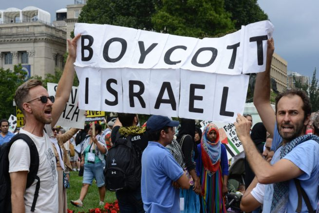 "Activists near the White House hold a ""Boycott Israel"" banner during a rally for Palestine. August 2, 2014. (Flickr / Stephen Melkisethian)"