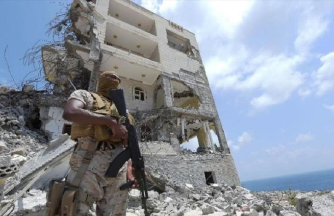 A Saudi military member stands next to a damaged building in the area of the presidential palace in the southern city of Aden. September 27, 2015. (Flickr / Ahmed Farwan)