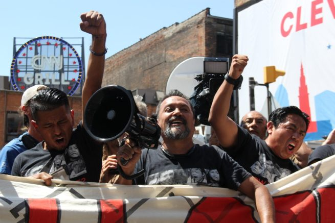 n this July 19, 2016 photograph, Latino activists cheer as they block the Quicken Loans Arena, site of the Republican National Convention in Cleveland, Ohio, with banners designed to look like a brick wall. (MintPress News / Desiree Kane)