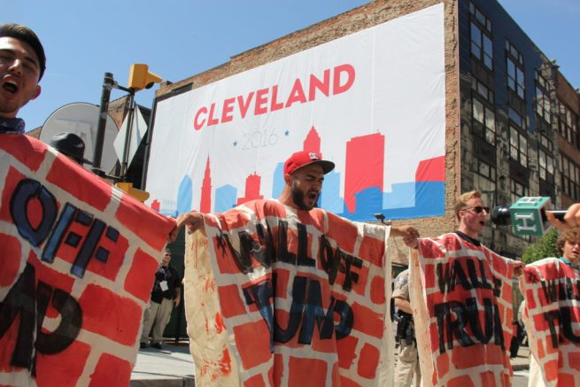 "In this July 20, 2016 photograph, activists ""Wall Off Trump"" with special costumers, blocking access to the Quicken Loans Arena, site of the 2016 Republican National Convention. (MintPress News / Desiree Kane)"