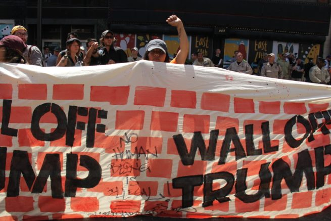 "July 19, 2016. An activist holds up a fist behind a ""Wall Off Trump"" banner, painted with a brick wall pattern and inscried ""No human being is illegal."" RNC 2016. (MintPress News / Desiree Kane)"