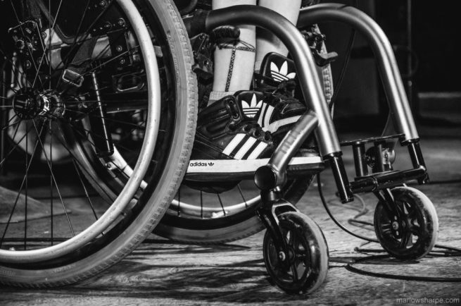 A close up of Kalyn wearing her Adidas in the foot rests of her wheelchair. (Copyright marlowsharpe.com, used with permission.)