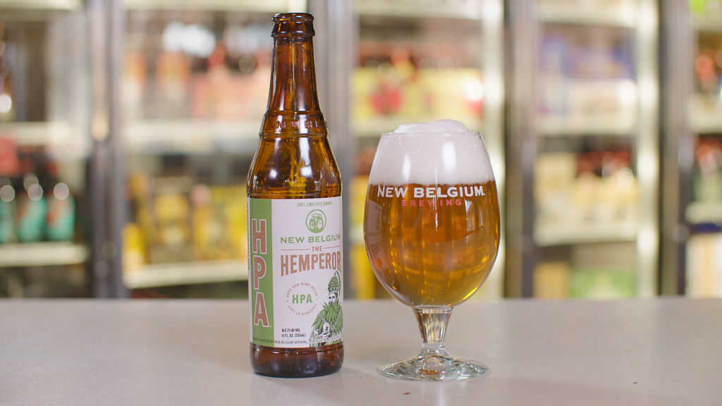 A bottle and a foamy glass of hemp beer sit atop a counter in a liquor store.